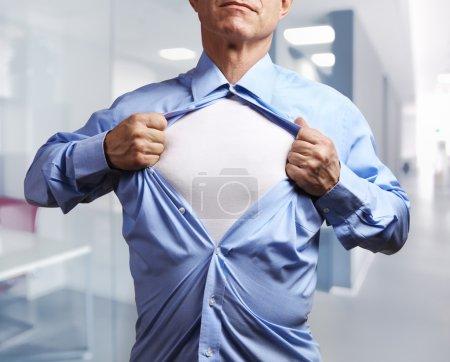 Photo pour Un super héros. Mature homme d'affaires arrachant sa chemise sur fond de bureau - image libre de droit