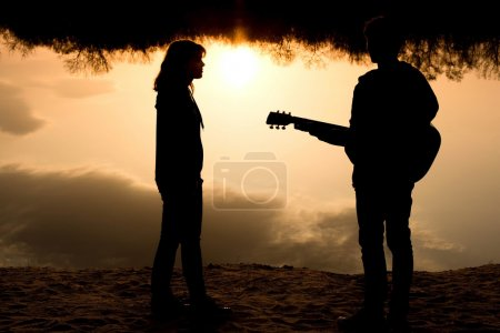 Silhouette of a young boy and girl on the beach wi...