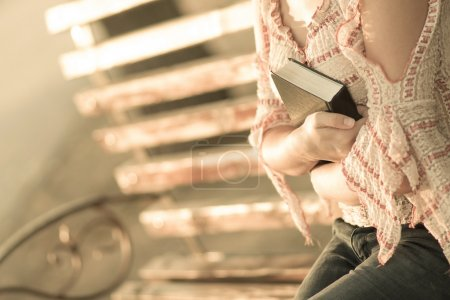 Woman hugging a book on a bench
