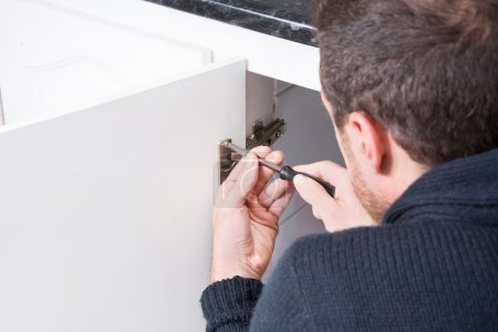 Man fixing a cabinet with a screwdriver