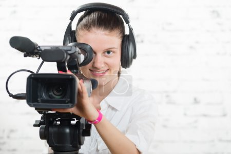 a pretty young woman with a professional  movie camera