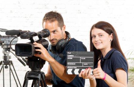 Photo pour Un caméraman et une jeune femme avec une caméra de film - image libre de droit