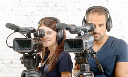 a man and a woman with professional video cameras