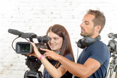 Photo pour Un jeune homme et une jeune femme cameramen avec caméra vidéo professionnelle - image libre de droit
