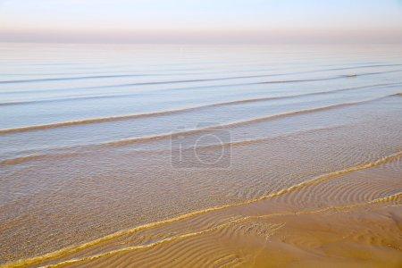 Photo pour Fond avec mer surf petites vagues sur les eaux peu profondes de la mer Baltique à Jurmala dans la lumière rose douce du soleil couchant - image libre de droit