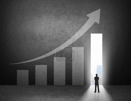 Photo pour Silhouette d'homme d'affaires debout devant le graphique de croissance sur le mur . - image libre de droit