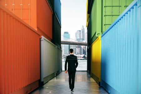 Businessman between cargo containers