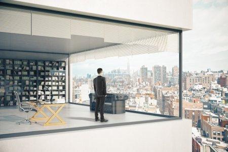 Photo pour Extérieur de bâtiment de voir-à travers avec des fenêtres panoramiques, homme d'affaires pensif, lieu de travail, divan et étagère sur l'arrière-plan de ville. Rendu 3d - image libre de droit