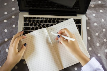Photo for Young girl writes in diary on laptop - Royalty Free Image