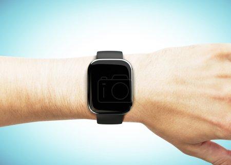 Photo pour Montre intelligente à portée de main sur fond bleu - image libre de droit