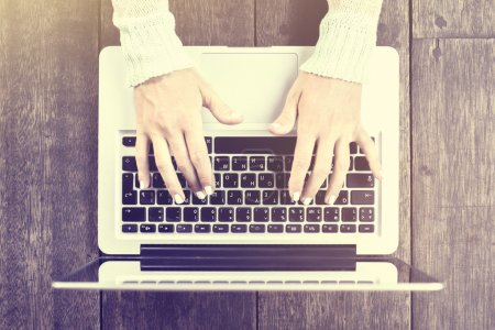 Photo pour Fille mains dactylographier sur ordinateur portable sur une table en bois - image libre de droit