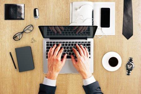 Männerhände mit Laptop, Tagebuch, Kaffeebecher, Uhren und anderem Zubehör