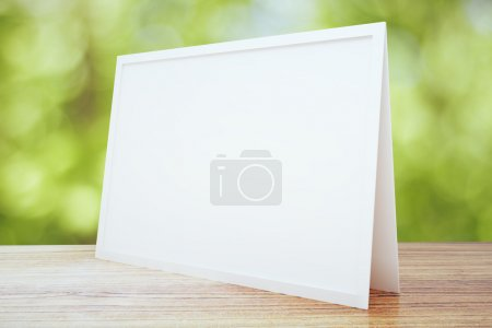 Blank white postcard on wooden table outdoor, mock up