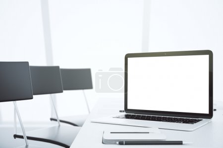 Blank white laptop screen on the table with chairs in modern off