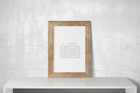 Photo for Blank wooden picture frame on white table and concrete floor, mock up - Royalty Free Image