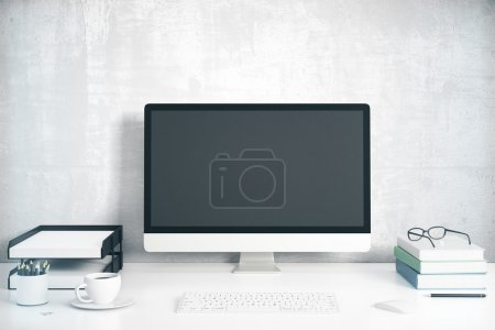 Blank black computer screen with office accessories on white tab