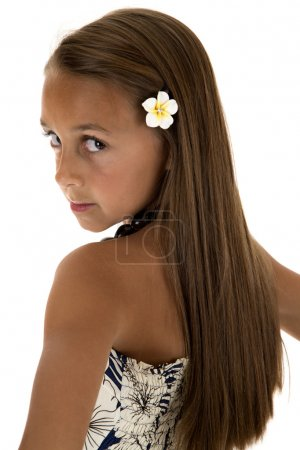 Beautiful tan girl wearing island dress looking over her shoulde