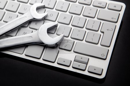 Photo for Electronic technical support concept - spanners on computer keyboard - Royalty Free Image