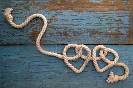 Photo pour Corde de laisse dans la forme de coeur sur la table en bois - image libre de droit