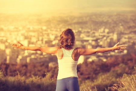 Photo for Young woman spreading hands wide open with city on background. Freedom concept. Love and emotions, woman happiness. Toned image - Royalty Free Image