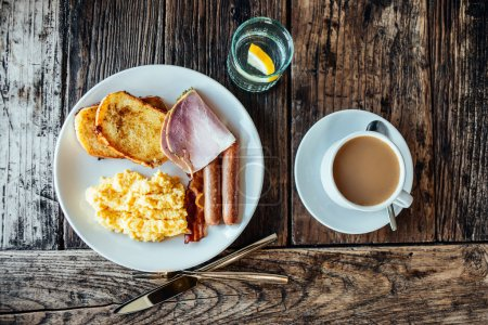 Photo for Breakfast served on wooden table - scrambled eggs, french toast, different cold meat cuts  and coffee. - Royalty Free Image