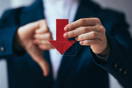 Business person holds red arrow and shows thumb do...
