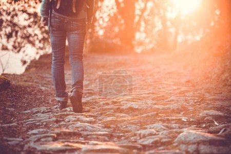 Photo pour Marcher ou courir jambes, l'aventure et l'exercice dans les montagnes sur route rocheuse au coucher du soleil. Image tonique - image libre de droit