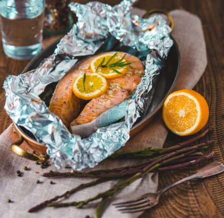 Photo for Salmon steak baked with lemon and herbs in foil - Royalty Free Image