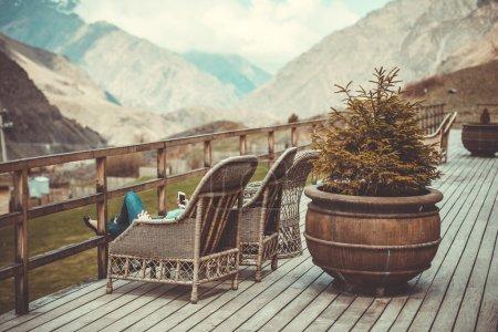 Foto de Chica sentada en la terraza con hermosa vista a la montaña. Tonos de la imagen - Imagen libre de derechos