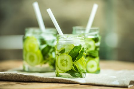 Photo for Three retro glass jars of lemonade with cucumber and mint on wooden table - Royalty Free Image