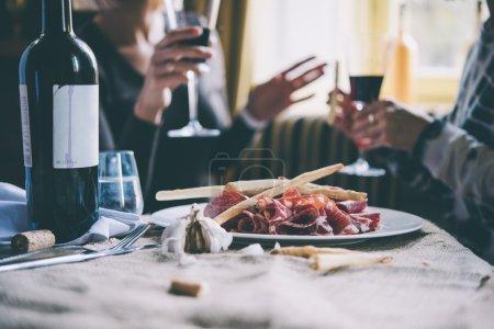 Photo pour Restaurant ou table de bar avec assiette de hors-d'œuvre et vin. Deux personnes parlent en arrière-plan - image libre de droit