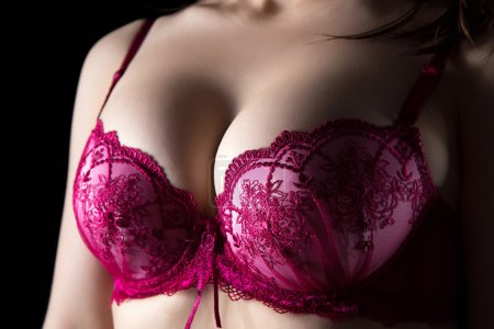 Womans breast on black background