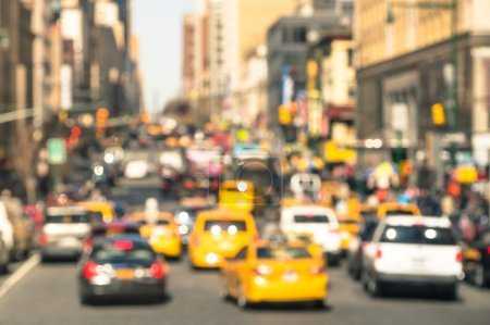 Rush hour with defocused cars and yellow taxi cabs - Traffic jam in Manhattan downtown - Blurred bokeh postcard of New York City with warm sunny day color tones - Real life transportation concept