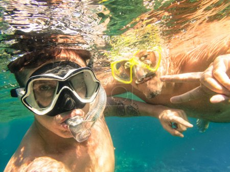 Adventurous best friends taking selfie snorkeling underwater - Adventure travel lifestyle enjoying happy fun moment - Trip together around Philippines wonders - Soft focus due to water density