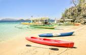 White sand beach with longtail boats and kayaks in Coron Palawan - Beautiful tropical destination in Philippines - Travel concept to nature wonders around the world - Warm sunny afternoon color tones