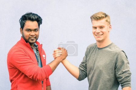 Indian and caucasian men shaking hands in a modern handshake to show each other friendship and respect - Best friends having arm wrestling against racism on blue wall - Soft desaturated filtered look