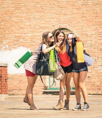 Group of happy friends with shopping bags taking a selfie in the city center - Girlfriends walking and having fun in the summer around the old town - University students during a break in a sunny day