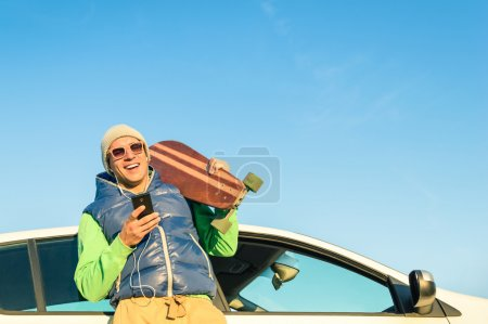 Young hipster man with smartphone listening music next his car - Concept of modern technologies mixed with a vintage travel lifestyle - Autumn winter youth alternative fashion in a sunny day trip