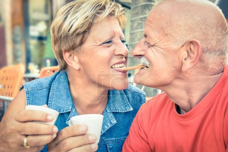 Happy playful senior couple in love tenderly enjoying a cup of coffee - Joyful elderly active lifestyle - Man having fun and smiling with her wife in a bar cafe restaurant during vacation