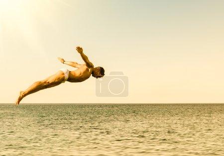 Foto de Buzo de acantilado saltando en el mar contra el cielo al atardecer - concepto de la libertad y la sensación despreocupada sintiendo la conexión pura con la naturaleza - Imagen libre de derechos