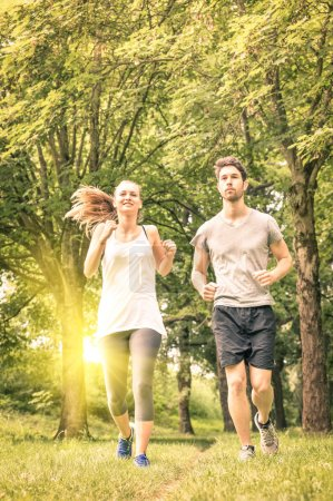 Happy couple jogging in the park - Young man and woman sharing workout and sport activity - Male and female fitness models running together in the nature at sunset