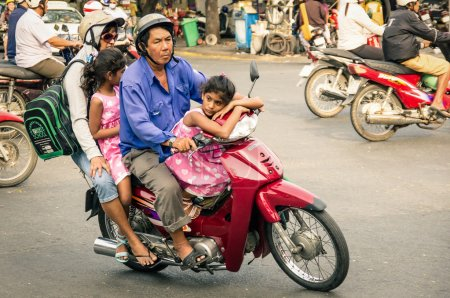 HO CHI MINH CITY, VIETNAM - FEBRUARY 6, 2013: full family driving a scooter in the city traffic. There are approximately 340,000 cars and 3,5 million motorcycles in the city.