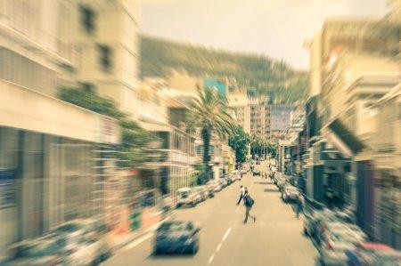 Photo pour Personnes et voitures se déplaçant sur Longstreet dans le centre-ville du Cap avant le coucher du soleil - navetteurs marchant dans le quartier d'affaires sud-africain - Zoom radial se déconcentrant sur un look filtré vintage - image libre de droit