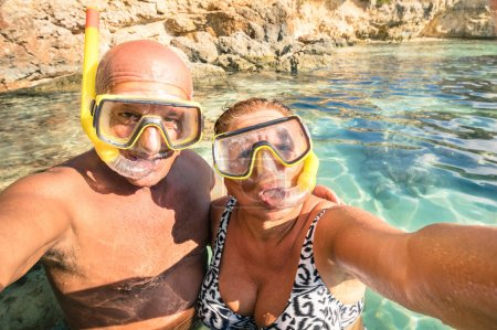 Senior happy couple taking a selfie at Blue Lagoon in Gozo and Comino - Travel to mediterranean island of Malta - Concept of active elderly and fun around the world experimenting new technologies