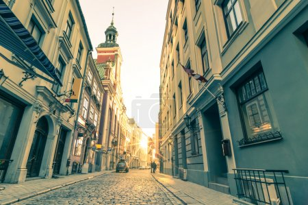 Vintage retro travel postcard of a narrow medieval street in old town Riga at sunset with sun reflection - Latvia - European capital of culture 2014
