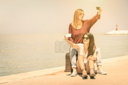 Hipster girlfriends taking a double selfie at wharf docks - Concept of friendship and fun with new trends and technology - Best friends fixing the moment with modern smartphone