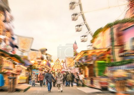 Crowd of people walking at luna park on a radial zoom defocusing - Multicolored fun stands at german Christmas market - Ferris wheel and colorful wooden houses at Berlin amusement area in winter time