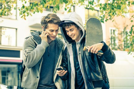 Young hipster brothers having fun with smartphone - Best friends sharing free time with new trends technology - Guys enjoying everyday life moments texting connected with modern smart phone device
