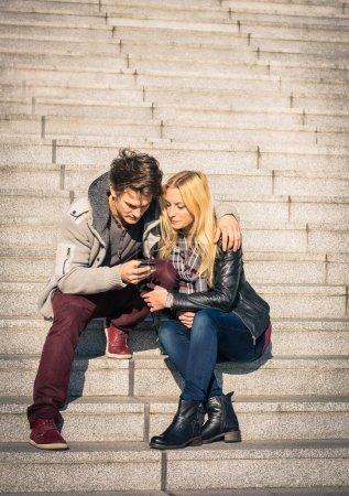 Photo pour Couple hipster amoureux s'amuser avec smartphone - Concept moderne de connexion dans une relation avec la technologie de la téléphonie mobile - Style de vie urbain de la ville représentant la vie quotidienne relation - image libre de droit