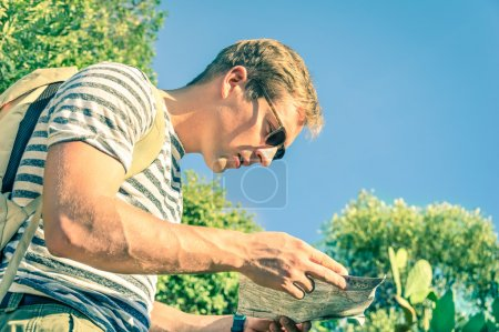 Profile of traveler handsome man searching right direction on map - Concept of carefree travel and journey around the world - Freedom and adventurous lifestyle on a vintage filtered look